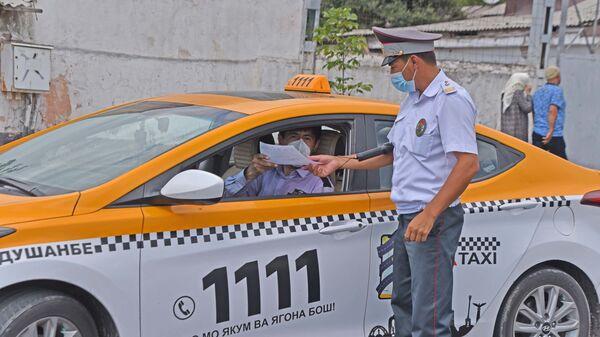 Сотрудник милиции проверяет документы у водителя такси в Душанбе - Sputnik Тоҷикистон