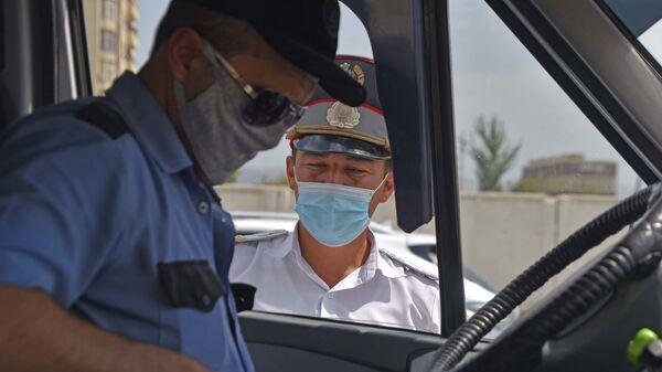 Сотрудник милиции проверяет документы у водителя маршрутки в Душанбе - Sputnik Таджикистан