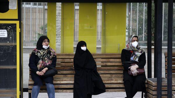 Иранские женщины сидят на автобусной остановке - Sputnik Тоҷикистон