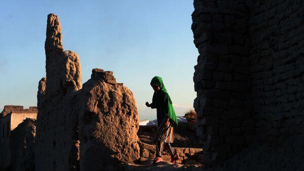 Афганская девочка проходит мимо руин здания - Sputnik Тоҷикистон