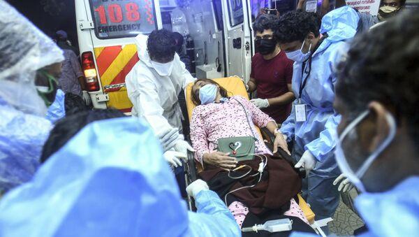 Эвакуация раненных при падении пассажирского самолета Boeing 737 Air India Express в индийском городе Кежикоде, штат Керала, Индия - Sputnik Тоҷикистон