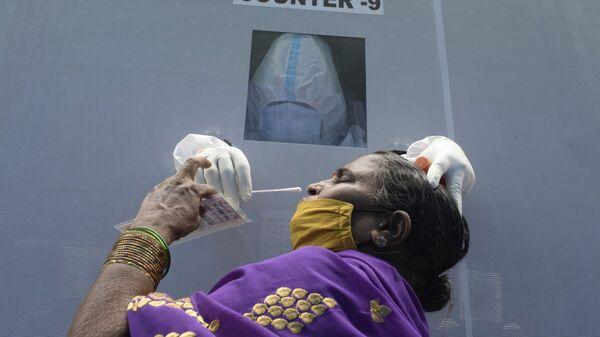Женщина в мобильном пункте сдачи теста на коронавирус в Хайдарабаде, Индия  - Sputnik Тоҷикистон