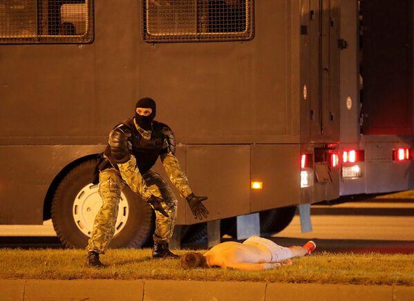 Сотрудник белорусских правоохранительных органов жестом указывает на раненого протестующего Евгения Зайчкина, архивное фото - Sputnik Таджикистан