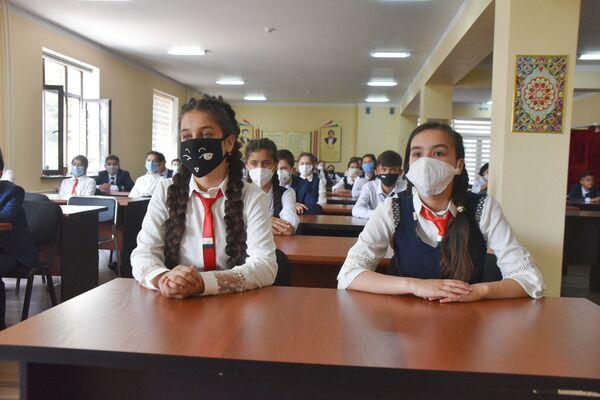 Школьники сидят за партой в защитных масках - Sputnik Таджикистан