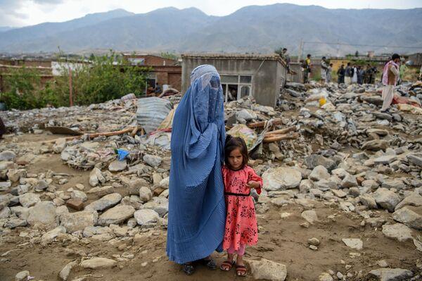 Женщина с ребенком у разрушенного здания после наводнения в Афганистане - Sputnik Таджикистан