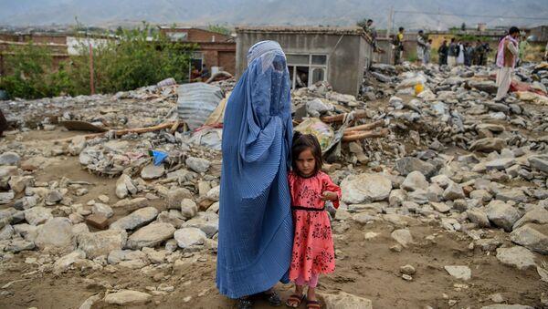 Женщина с ребенком у разрушенного здания после наводнения в Афганистане - Sputnik Тоҷикистон