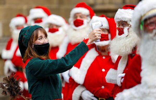 Женщина в костюме эльфа позирует с выпускниками Школы Санта-Клауса Ministry of Fun в Лондоне - Sputnik Таджикистан
