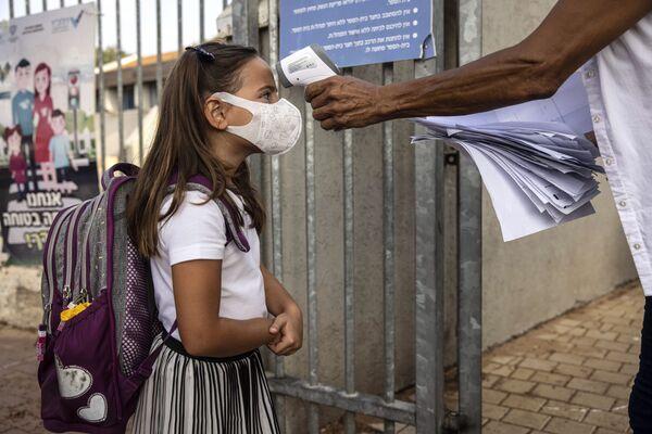 Девочка в маске во время измерения температуры в первый день школы в Израиле  - Sputnik Таджикистан