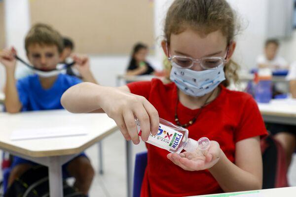 Израильская девочка протирает руки антисептиком в первый день школы в Израиле  - Sputnik Таджикистан