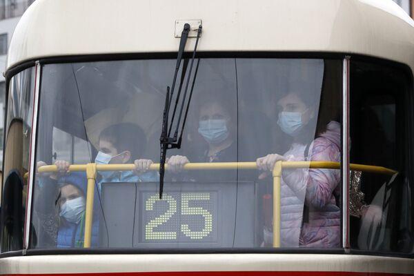 Люди в защитных масках едут в пражском трамвае - Sputnik Таджикистан