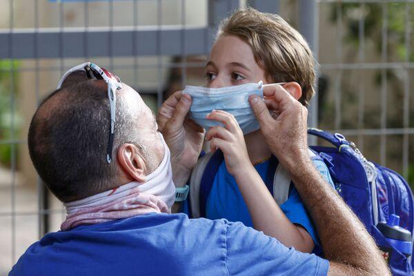 Отец надевает защитную маску на дочь-школьницу - Sputnik Таджикистан