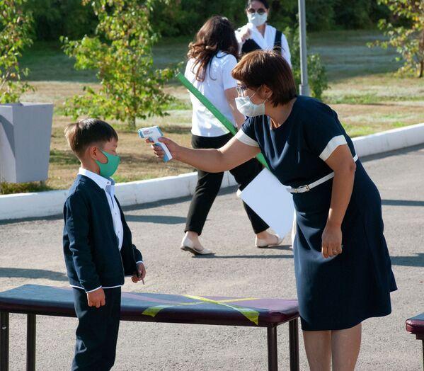 Учитель измеряет температуру первокласснику перед уроком в Казахстане - Sputnik Таджикистан