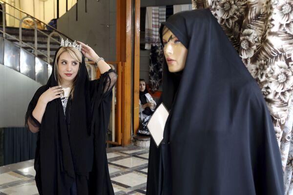 Девушка меряет корону в магазине в Тегеране  - Sputnik Таджикистан