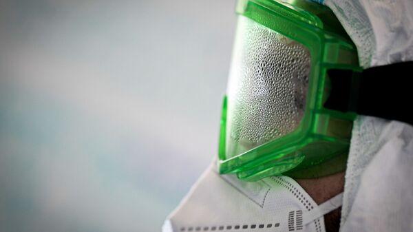 Врач в запотевших защитных очках во время работы в госпитале для лечения зараженных коронавирусной инфекцией COVID-19 - Sputnik Таджикистан