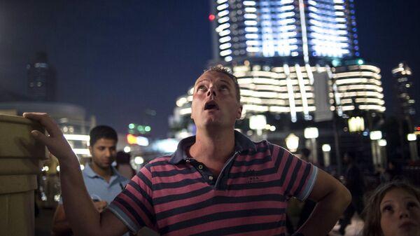 Турист смотрит на самый большой небоскреб Бурдж-Халифа в Дубае. - Sputnik Таджикистан