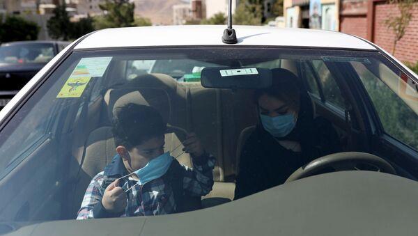 Ученик первого класса с матерью в машине в первый учебный день в школе в Тегеране  - Sputnik Тоҷикистон