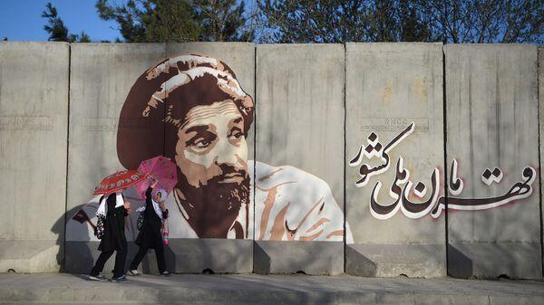 Школьницы идут по улице Кабула на фоне граффити с изображением Ахмада Шах Масуда - Sputnik Тоҷикистон
