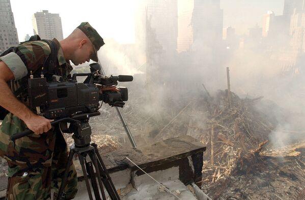 Оператор во время съемки разрушений на месте Всемирного торгового центра после атаки в Нью-Йорке  - Sputnik Таджикистан