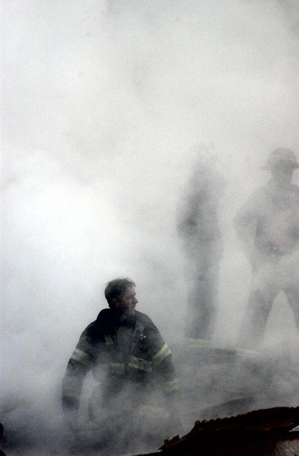 Пожарный в дыму от разрушения Всемирного торгового центра 11 сентября в Нью-Йорке  - Sputnik Таджикистан