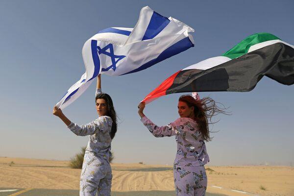 Модели из Израиля и ОАЭ с флагами стран во время фотосессии для модного бренда FIX's Princess Collection в Дубае  - Sputnik Таджикистан