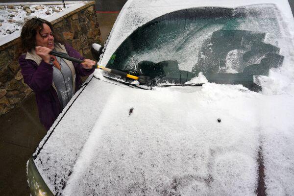 Жительница Джорджтауна во время чистки машины от снега - Sputnik Таджикистан