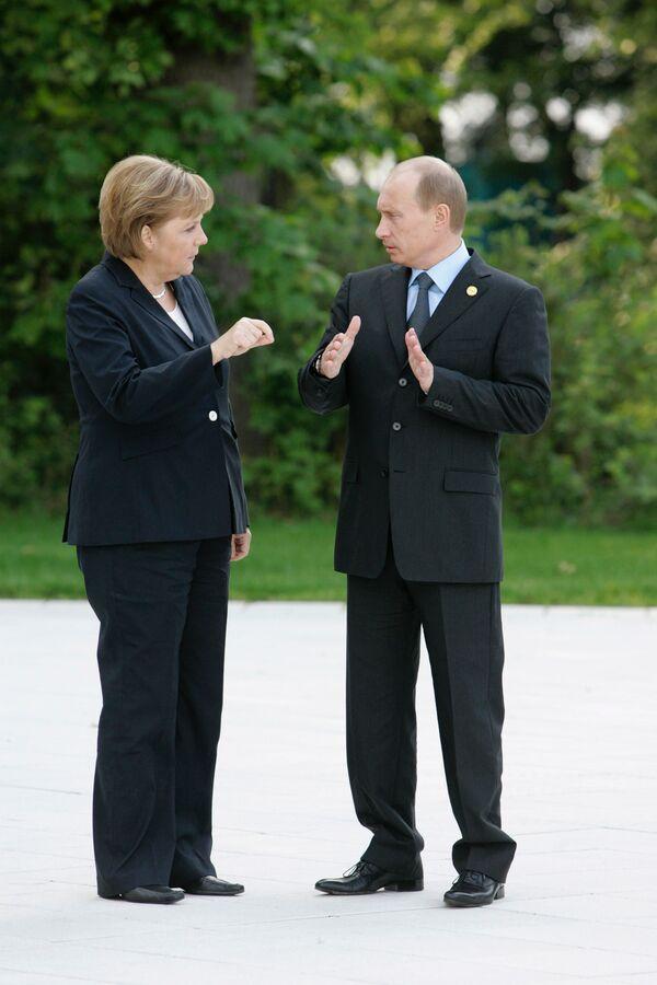 Федеральный канцлер Германии Ангела Меркель и президент России Владимир Путин с яркой жестикуляцией обсуждают что-то перед началом беседы в Хайлигендамме. 6 июня 2007 года. - Sputnik Таджикистан