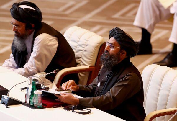 Лидер движения Талибан (запрещено в РФ)  во время переговоров с правительством Афганистана в Катаре - Sputnik Таджикистан