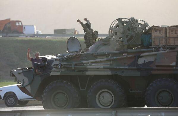 Военнослужащий Азербайджана управляет бронетранспортером и приветствует граждан, собравшихся на обочине дороги в Баку - Sputnik Таджикистан