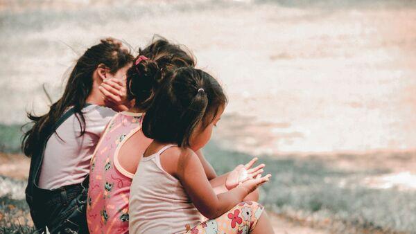 Маленькие девочки сидят на траве - Sputnik Тоҷикистон