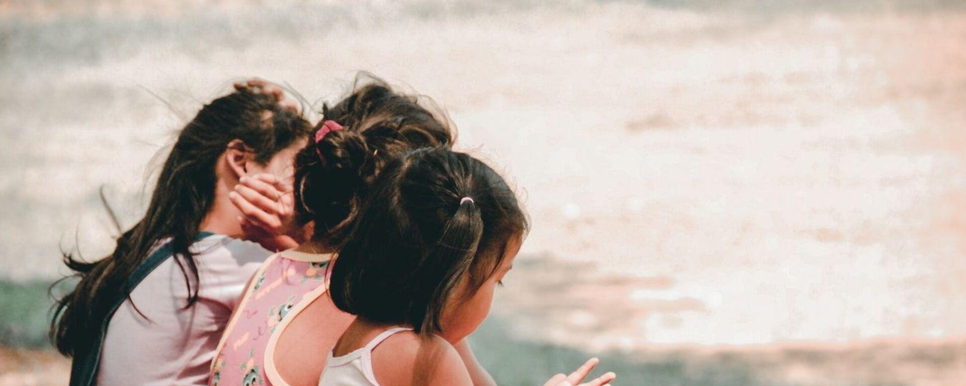 Маленькие девочки сидят на траве - Sputnik Тоҷикистон, 1920, 02.10.2020