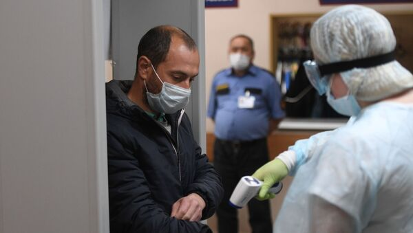 Медицинский работник измеряет температуру у мужчины - Sputnik Таджикистан