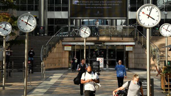 Пандемия коронавируса COVID-19. Просьба носить маски на экране в деловом районе Кэнэри-Уорф в Лондоне - Sputnik Тоҷикистон