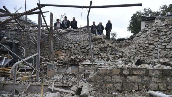 Мужчины смотрят на разрушения в жилом районе после обстрела азербайджанской артиллерией  - Sputnik Тоҷикистон