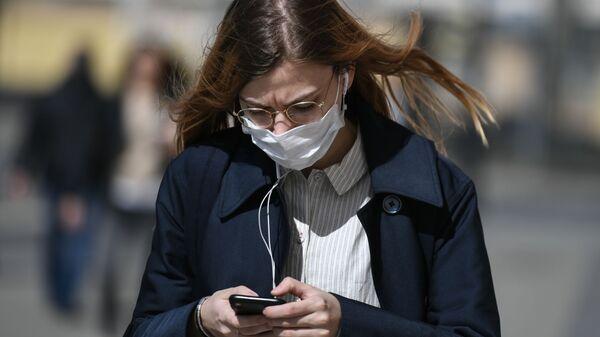 Девушка в защитной маске идет по улице - Sputnik Тоҷикистон