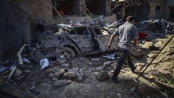 Мужчина идет среди обломков поврежденных домов в Гяндже, Азербайджан - Sputnik Тоҷикистон