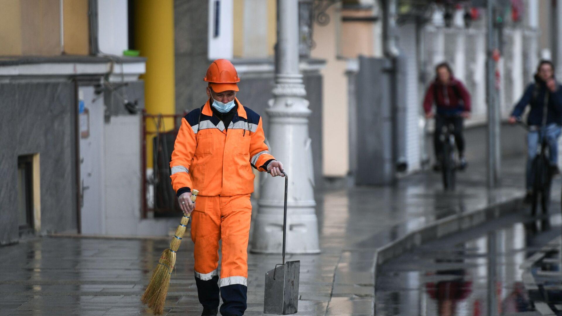 Сотрудник коммунальной службы убирает улицу в Москве, архивное фото - Sputnik Таджикистан, 1920, 23.08.2021