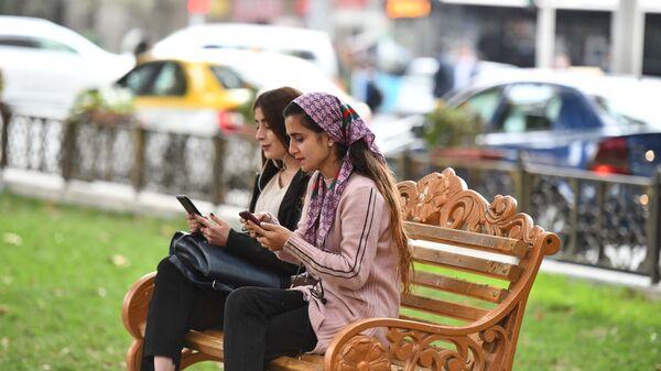 Девушки сидят на скамейке в парке - Sputnik Тоҷикистон