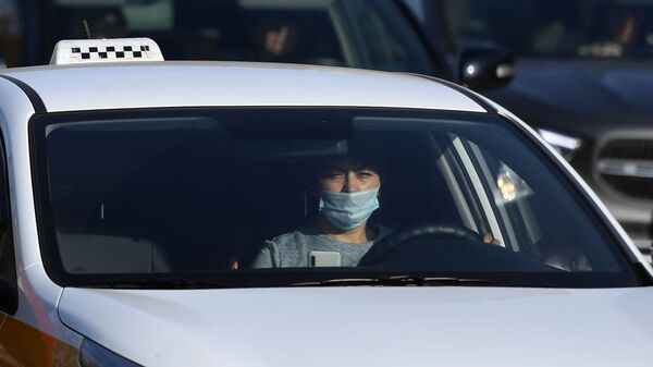 Водитель в защитной маске за рулем такси - Sputnik Таджикистан
