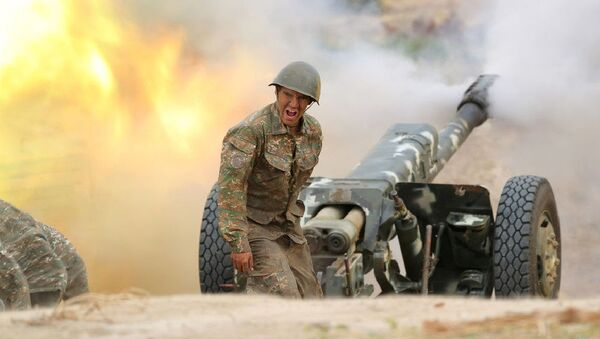 Военнослужащий стреляет из артиллерийского орудия во время боя с азербайджанскими силами в Нагорном Карабахе - Sputnik Таджикистан