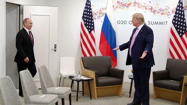 Президент США Дональд Трамп (справа) жестикулирует, когда президент России Владимир Путин прибывает на переговоры во время двусторонней встречи на полях саммита G-20 - Sputnik Таджикистан