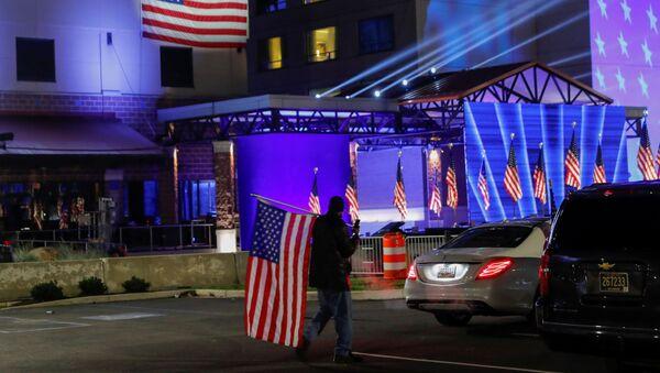 Сторонник Байдена с флагом в день выборов президента в штате Делавер, США - Sputnik Тоҷикистон