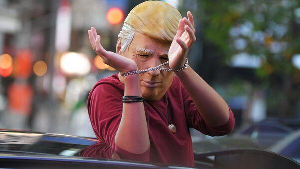 Человек в маске Дональда Трампа едет на машине по улице Нью-Йорка после новостей о победе на выборах президента США кандидата от Демократической партии Джозефа Байдена - Sputnik Таджикистан