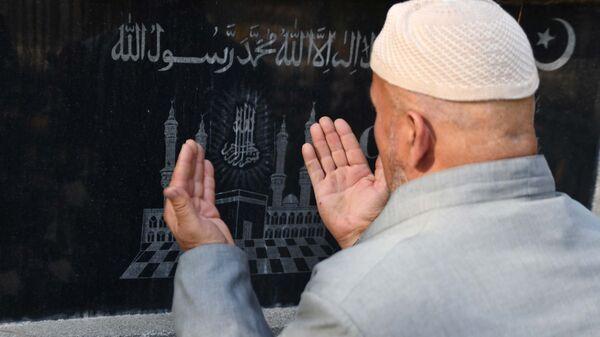 Мужчина совершает молитву на кладбище - Sputnik Тоҷикистон