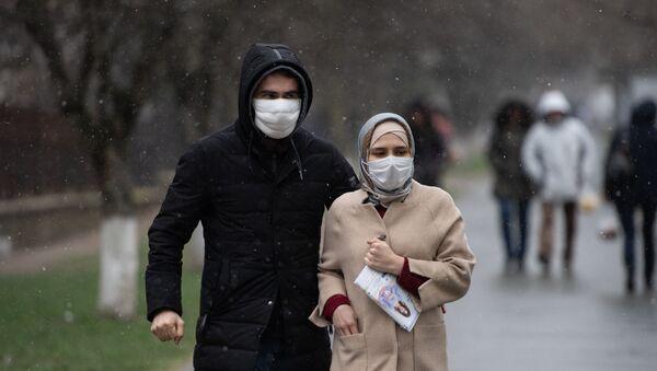 Люди в медицинских масках идут по улице  - Sputnik Тоҷикистон