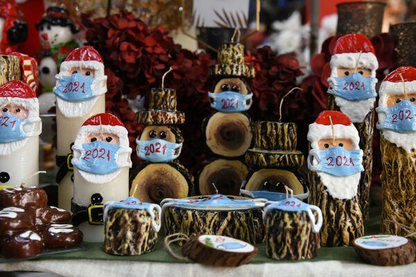 Рождественские свечи в виде Санта-Клаусов в масках в магазине в Греции  - Sputnik Таджикистан