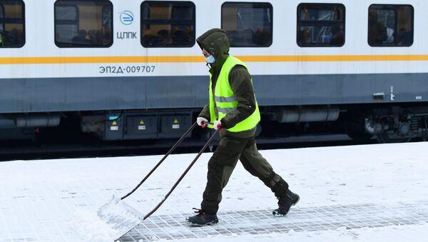 Сотрудник коммунальных служб во время уборки платформы на вокзале, архивное фото - Sputnik Таджикистан