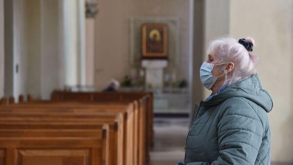 Женщина в защитной маске в одном из храмов во Львове - Sputnik Тоҷикистон
