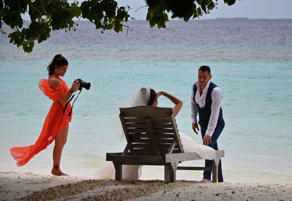 Молодожены фотографируются на пляже одного из Мальдивских островов, получивших звание World's Leading Destination 2020 - Sputnik Таджикистан