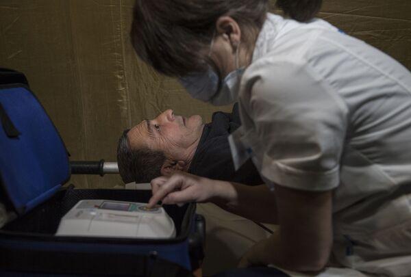 Медицинская сестра проводит электрокардиографию пациента на базе госпиталя развернутого Министерством обороны России на территории аэропорта в Степанакерте - Sputnik Таджикистан