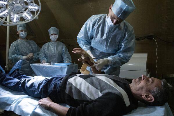 Медик оказывает помощь пациенту на базе полевого госпиталя развернутого Министерством обороны России на территории аэропорта в Степанакерте - Sputnik Таджикистан